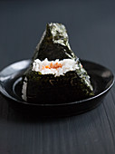 Two onigiri filled with salmon, one bitten (Japan)