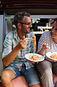 A couple eating spaghetti outside a camper van