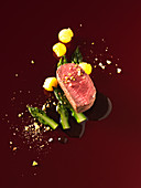 Lamb fillet with green asparagus and pineapple on date and mango sauce