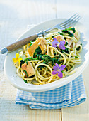 Spaghetti with smoked trout fillets and edible flowers