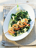 Wild herb spinach with a shrimp skewer