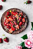 Vegane Schokoladen-Kokos-Tarte mit Erdbeeren und Pistazien