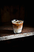 An iced latte in a glass against a dark background