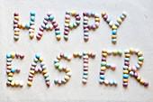 Schriftzug 'Happy Easter' aus bunten Schokoladenostereiern gelegt