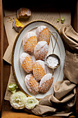 Gluten-free lemon madeleines with icing sugar on a platter