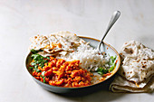 Vegan vegetarian curry with ripe yellow jackfruit served in ceramic bowl with rice, coriander and homemade flatbread