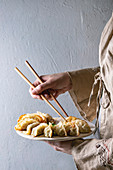 Fried asian dumplings Gyozas potstickers on white ceramic tray and wooden chopsticks in female hands