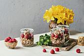 Layered dessert in jars: Biscuit, coffee cream, nuts, raspberries, fresh mint