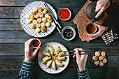 Personen am Tisch mit verschiedenen Dim Sum, Saucen und Tee (Asien)