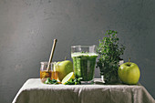 Green spinach kale apple honey smoothie in glass on linen table cloth with ingredients above