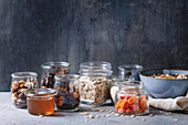 Variety of dried fruits, nuts, honey and oat flakes in bowl and different glass jars for cooking healthy breakfast muesli or granola energy bars