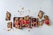 Homemade energy oats granola bars with dried fruits and nuts whole and broken wrapped in red paper