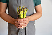 Man in grey apron before white background holding a bundle of green asparagus in his hands