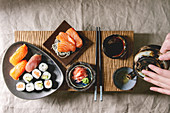 Sushi Set nigiri and sushi rolls on japanese wooden serving board with soy sauce, chopsticks, ceramic tea pot in hands