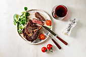 Grilled roasted sliced medium rare beef steak served in ceramic plate with green field salad, cherry tomatoes, cutlery, pepper, glass of red wine
