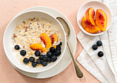 Oats, peach slices, blueberries and milk in a bowl for breakfast
