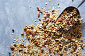 Almonds, oats, dried sultanas, coconut flakes and pepita seeds on a blue background