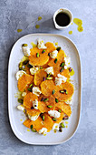 Orange, bocconcini and pistachio salad with a jug of spicy dressing