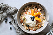 Healthy breakfast; bowl of muesli with sliced peaches and yoghurt