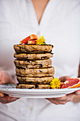 Woman holding a stack of pancakes with chocolate chips on a plate with flowers and grapefruit wedges