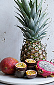 Pineapple, passion fruit halves, dragonfruit and mango with a white background