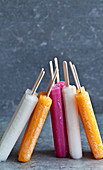 White, pink, and orange popsicles leaning against each other on a blue countertop and background