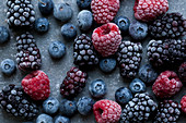 Frozen raspberries, blackberries and blueberries, photographed from above on a blue surface