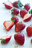 Strawberries, whole and halved, photographed from above on a white textured surface