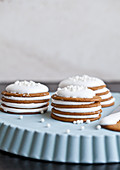 Ginger cookies, topped with marshmallow cream, and white candies, stacked on a blue tray