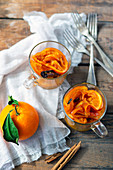 Squeezed slices of fresh oranges and cinnamon sticks placed inside glass cups and forks on wooden tabletop