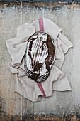 Frisch gebackener Laib Schwarzbrot auf Geschirrtuch