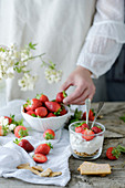 Chef using fresh juicy tasty strawberries while preparing creamy sweet dessert