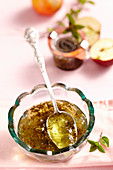 Mint and apple jelly in a glass bowl with a silver spoon