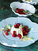 Panna cotta with wild strawberries and edible flowers