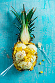 Pineaple and coconut sorbet in a pineapple with pineaple chunks and toasted coconut