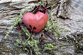 A pink decorative heart with herbs on a piece of wood