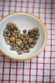 A heart of capers in a ceramic bowl
