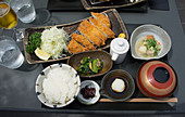 Tonkatsu with cabbage, sauce, rice, pickles, grated radish and miso soup (Japan)