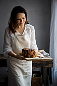Woman serving chocolate, tahini and halva babka with cardamom syrup