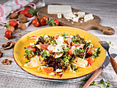 Fitness salad with figs, cheese, cherry tomatoes, walnuts and strawberries