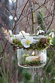 Windlicht mit Kränzchen aus Moos und Blüten von Christrose und Schneeglöckchen an Zweig gehängt