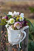 Sträußchen aus Blüten von Christrosen und Schneeglöckchen in Tasse