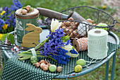 Osterdeko mit Strauß aus Hyazinthe, Traubenhyazinthe und Tulpen, Holz-Osterhase, Ostereier, Korb mit Steckzwiebeln, Schnur