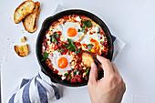 Shakshuka (Tomaten-Paprika-Pfanne mit Ei) in Gußeisenpfanne, Hand tunkt Röstbrot