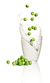 Peas falling into a glass of milk
