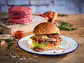 A juicy hamburger and raw hamburger patties