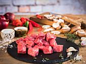 Rindfleisch für Gulasch, aus dem Bug geschnitten, Gemüse, Pilze und Gewürze