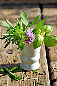 Basil, parsley and chive blossoms in a ceramic vase