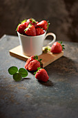 Fresh strawberries in a cup on a black surface