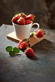 Frische Erdbeeren in Tasse auf schwarzem Blech